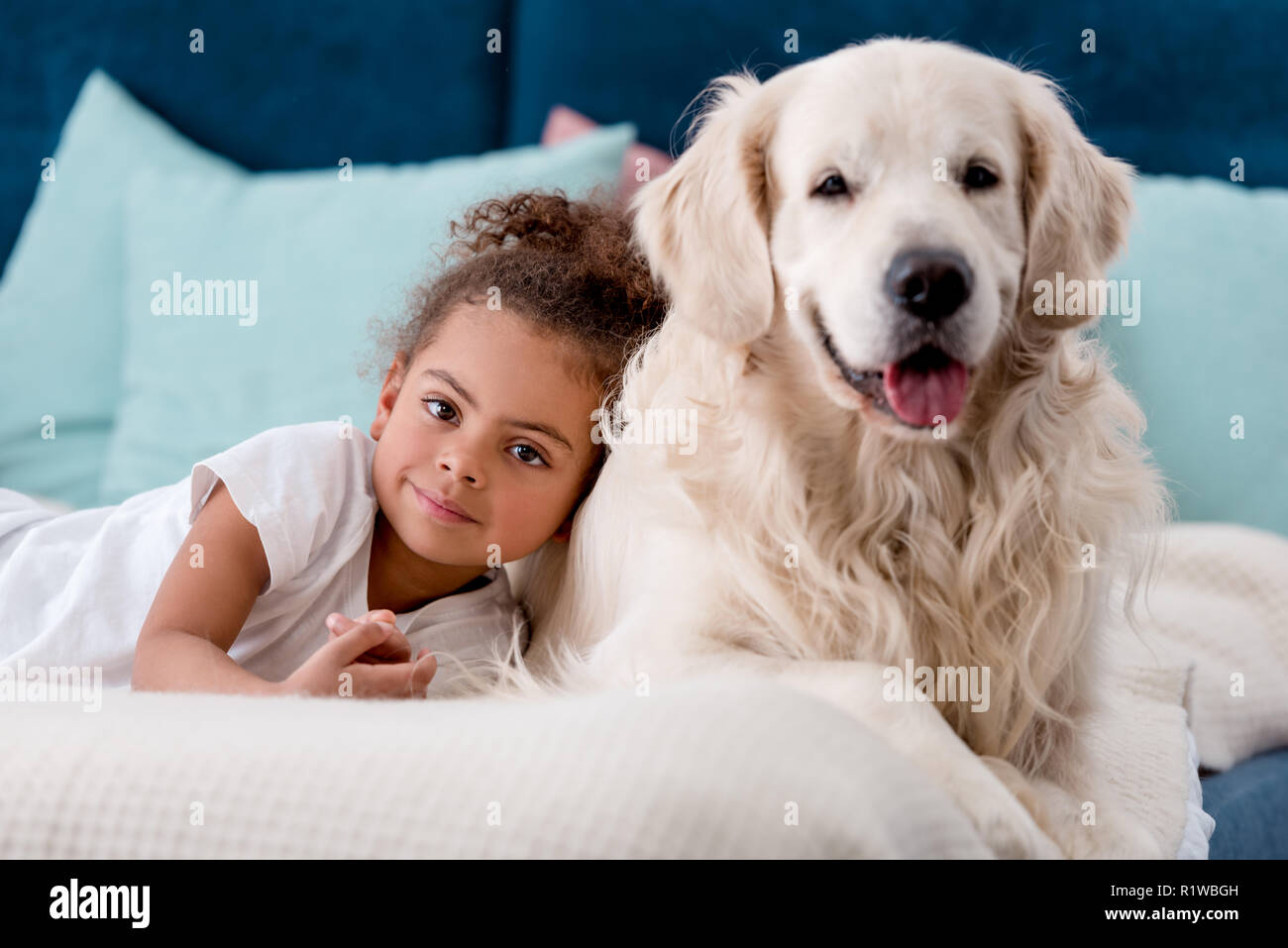 Adorable african american child with happy dog smiling at camera - Stock Image