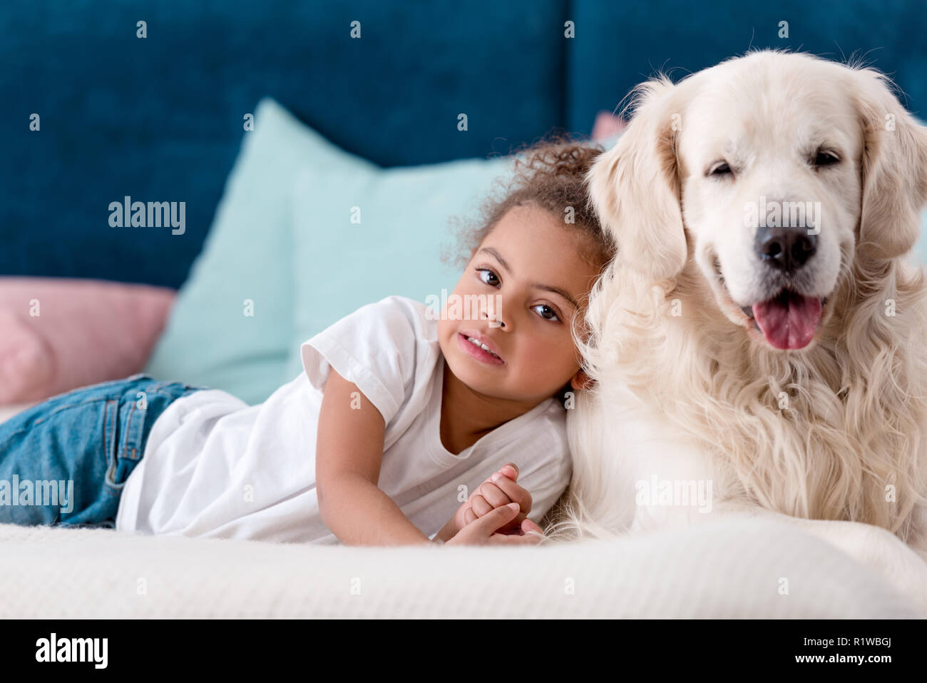 Adorable little african american kid with happy dog lying on bed - Stock Image