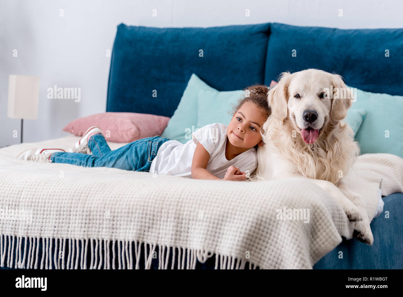 Adorable little african american kid with happy dog looking away while lying on bed Stock Photo