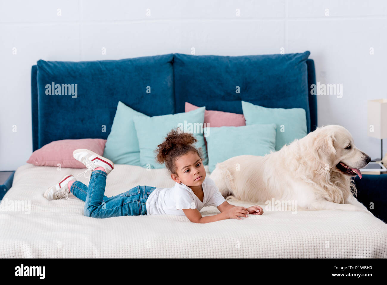 Cute little african american kid with happy dog lying on bed - Stock Image