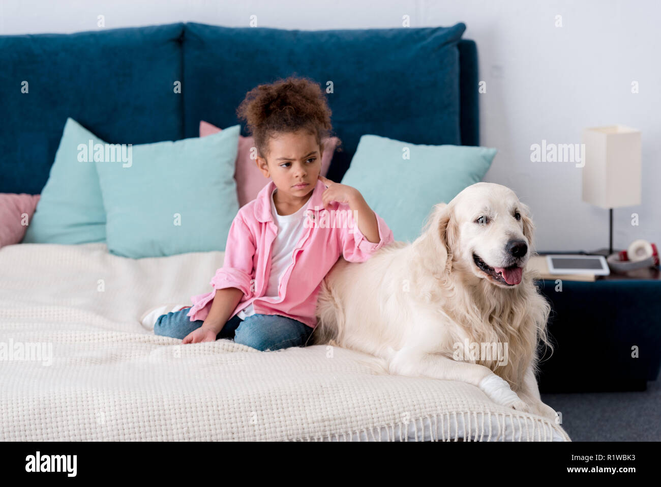Confused african american kid leaned on her retriever Stock Photo