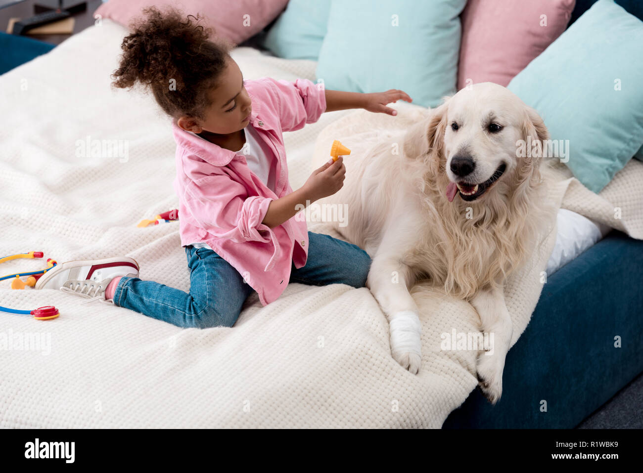 Cute african american kid playing doctor with her dog - Stock Image