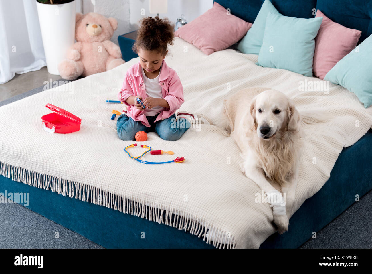 Cute african american child playing with toys on the bed with white dog lying beside - Stock Image