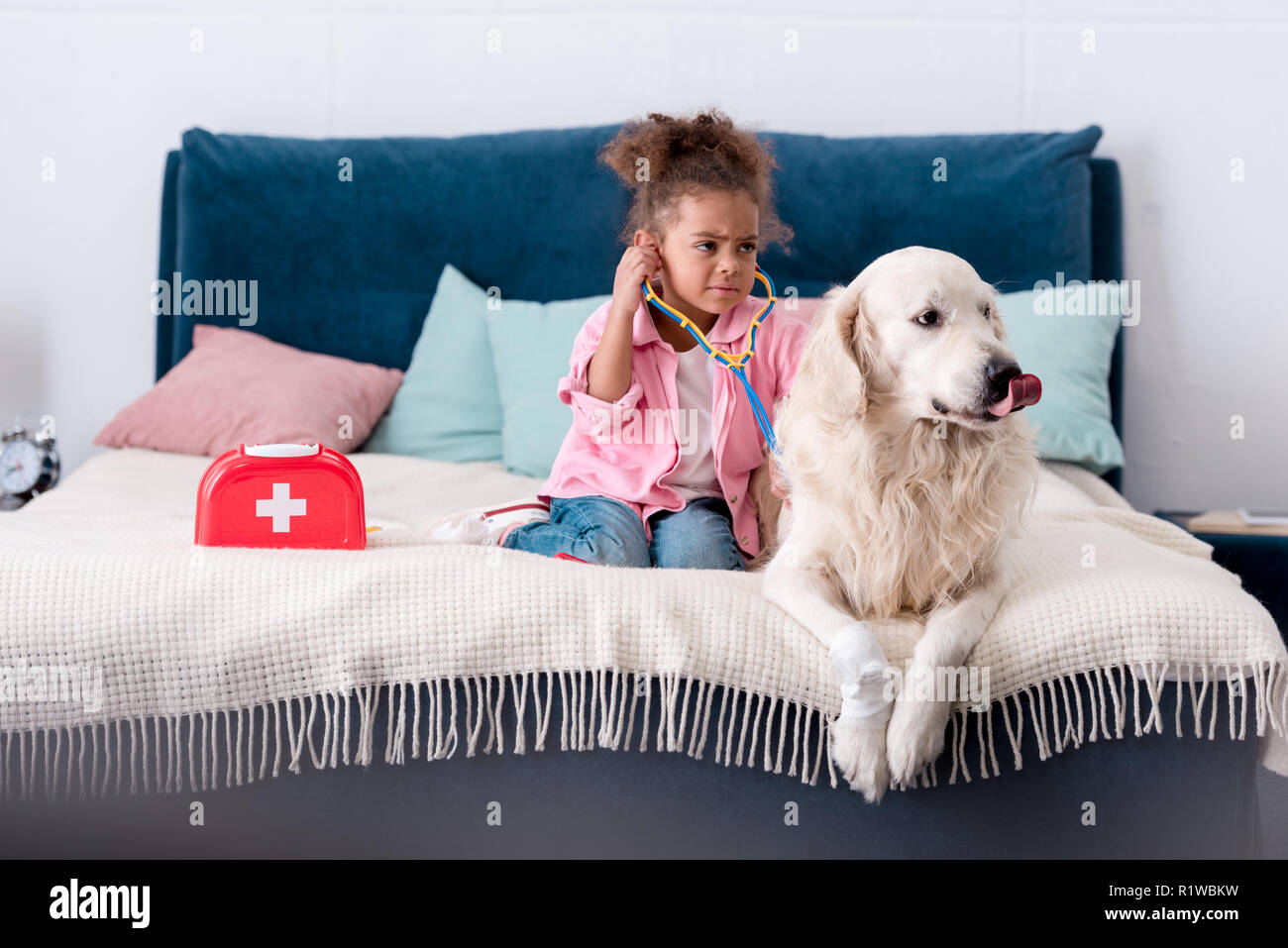 Discomposed african american kid playing with stethoscope and her dog Stock Photo