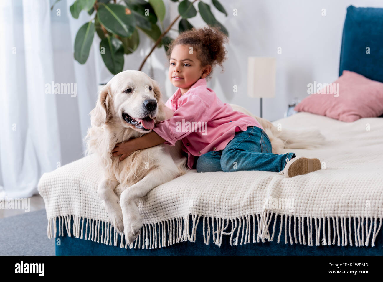 Cute african american kid sitting on the bed and  hugging her dog - Stock Image