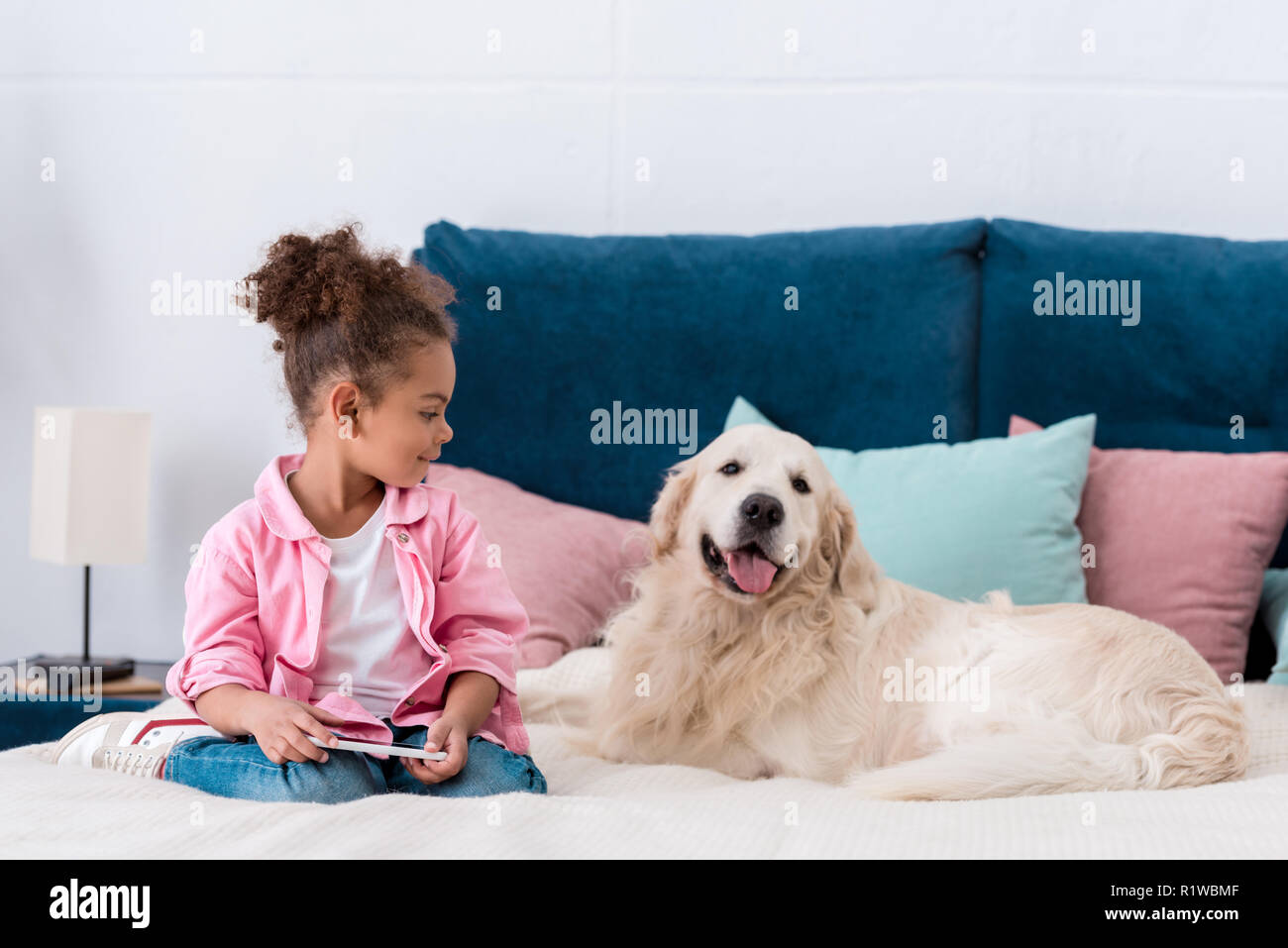 Curly african american kid sitting on the bed with smartphone and smiling golden retriever - Stock Image