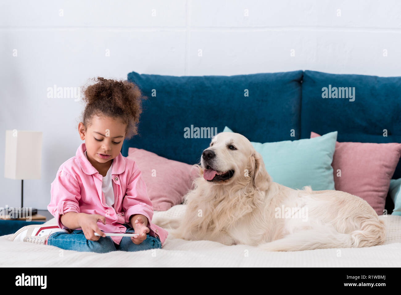 Curly african american kid sitting on the bed with retriever and looking in smartphone - Stock Image