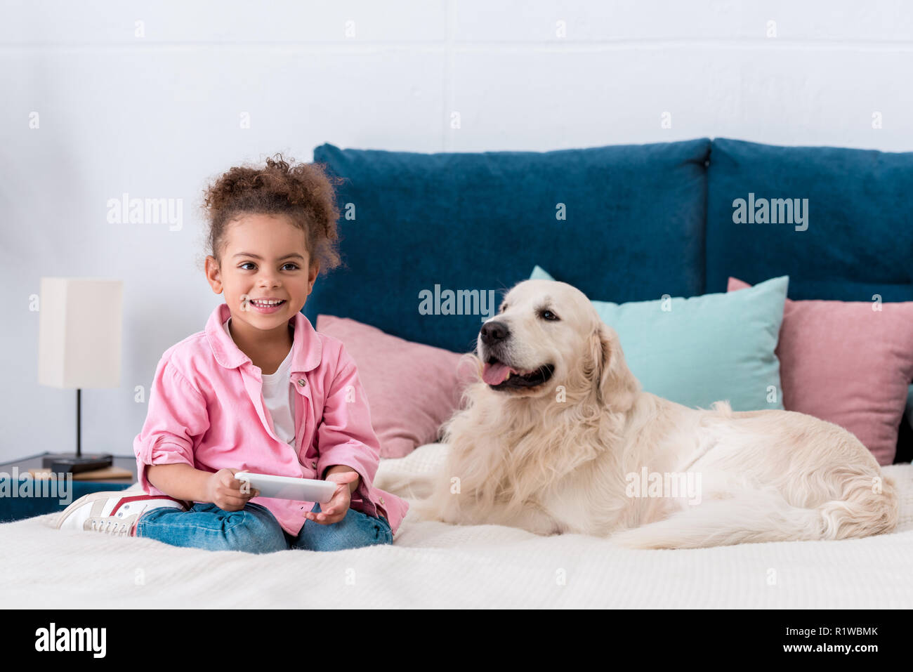 smiling african american kid sitting on the bed with smartphone and golden retriever - Stock Image
