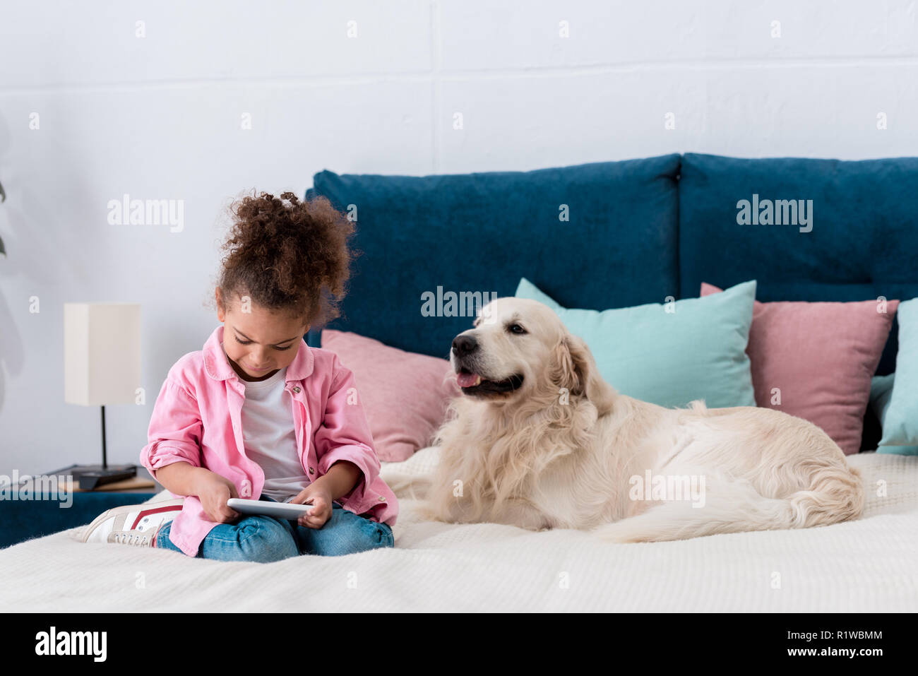 smiling african american kid sitting on the bed with golden retriever and playing with smartphone - Stock Image