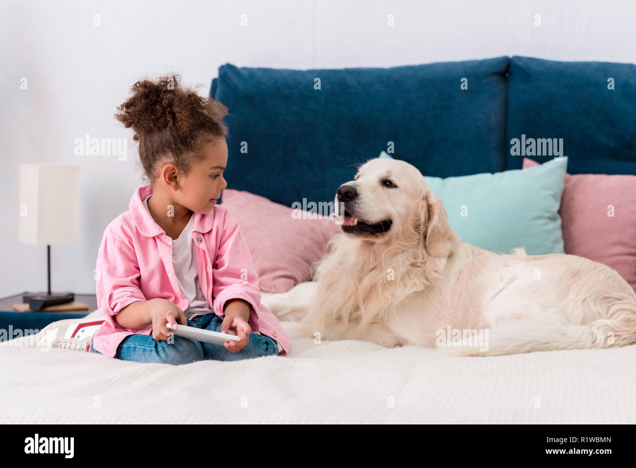 cute african american child sitting on the bed with golden retriever and playing with smartphone Stock Photo