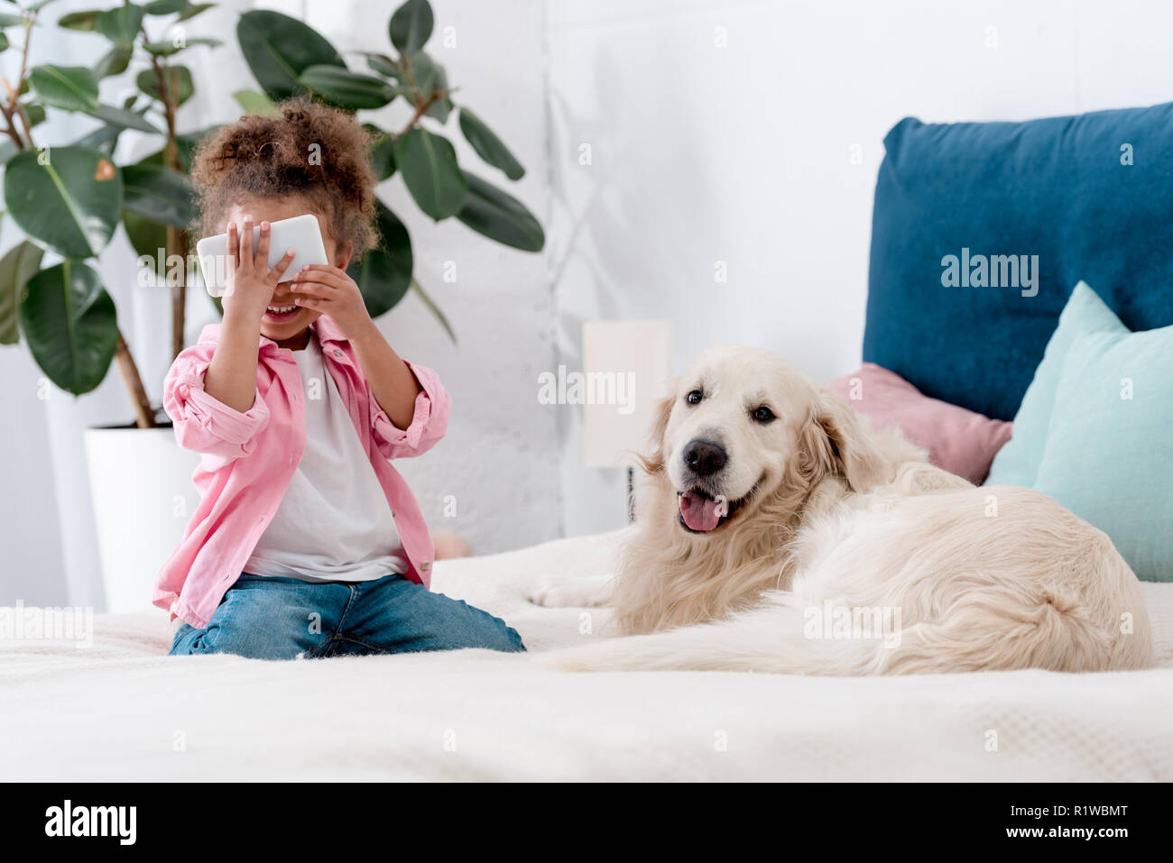 cute african american child sitting on the bed with retriever and holding smartphone near face Stock Photo
