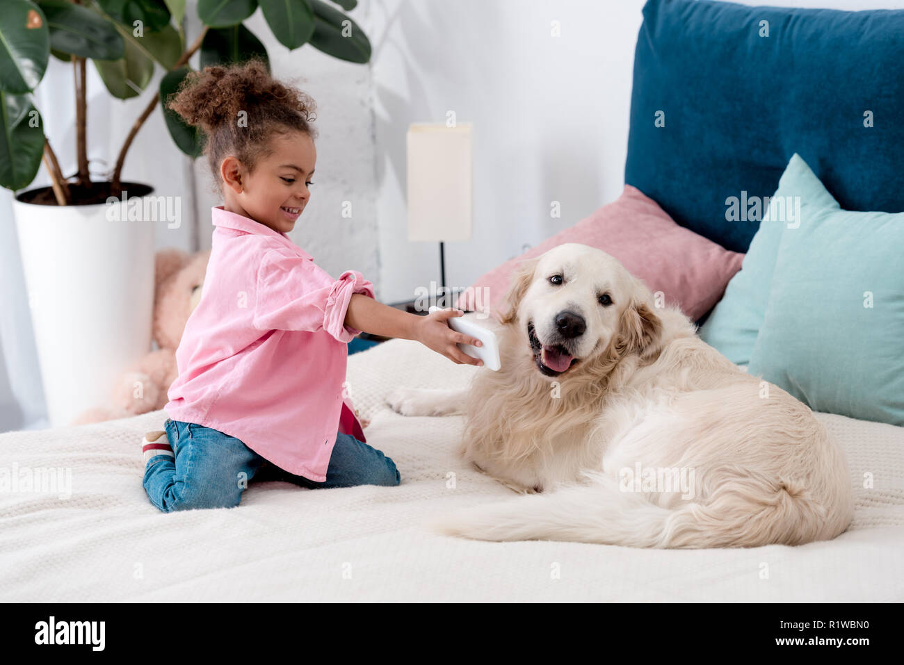 adorable african american child sitting on the bed and shows smartphone screen to dog - Stock Image