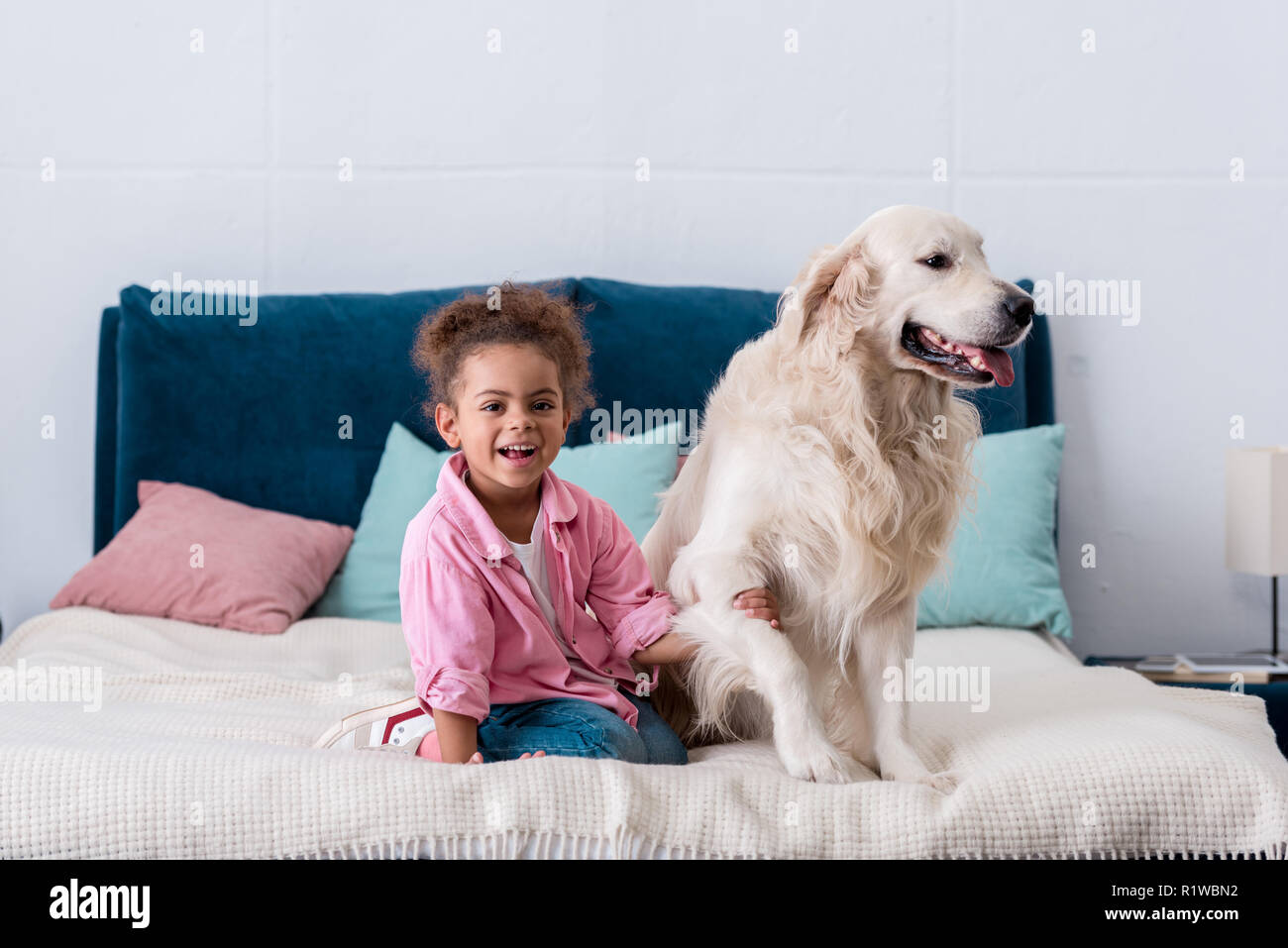 Smiling african american child sitting on the bed and holding dog paw - Stock Image