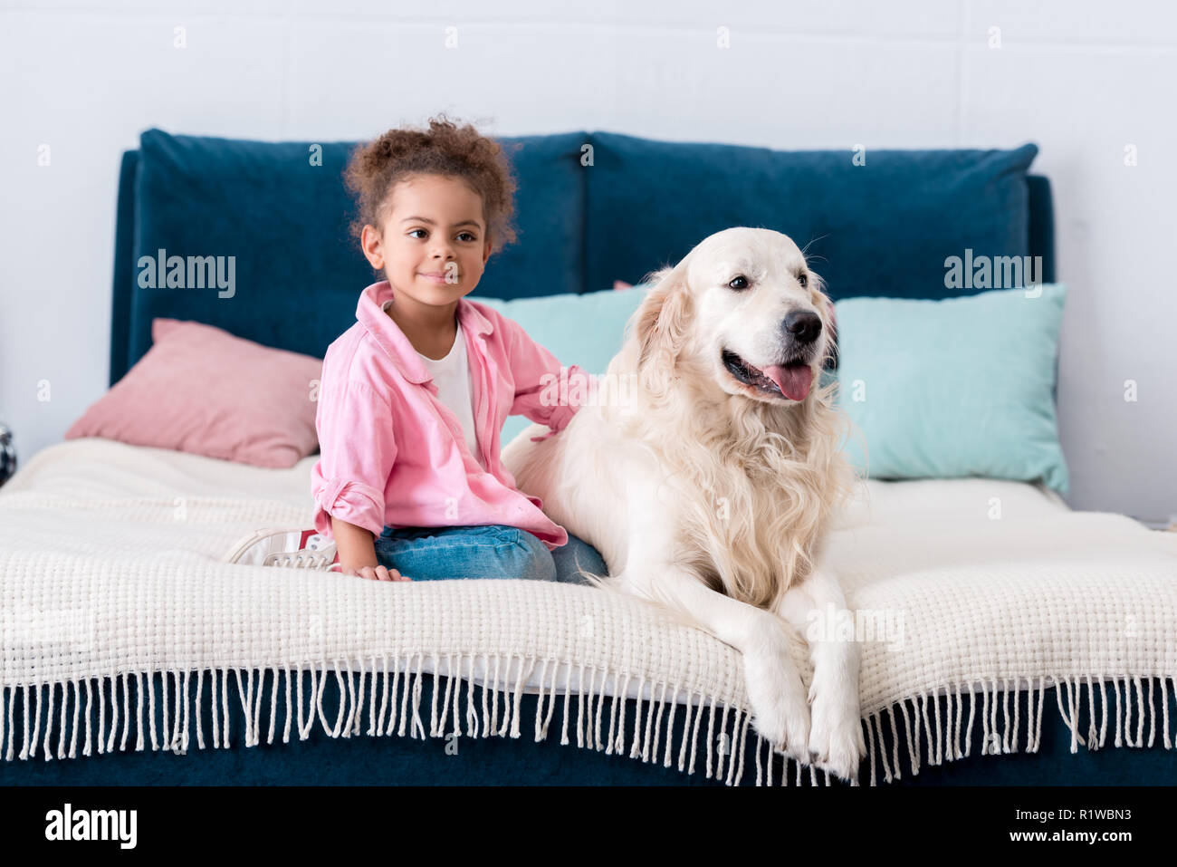 Cute african american child sitting on the bed with her dog beside - Stock Image