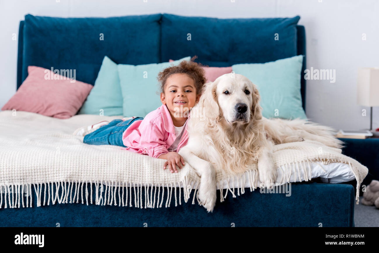 Smiling african american child lying on the bed with her golden retriever - Stock Image