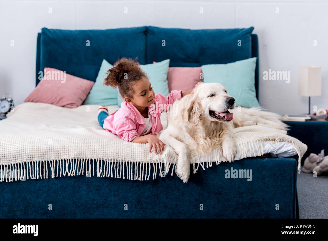 Adorable african american child lying on the bed and scratching the back of a dog - Stock Image