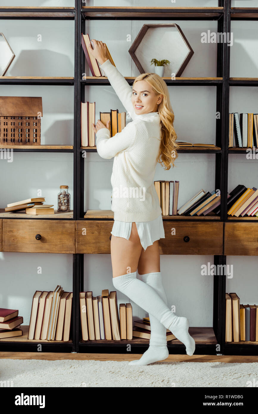 beautiful adult woman taking book from wooden rack - Stock Image