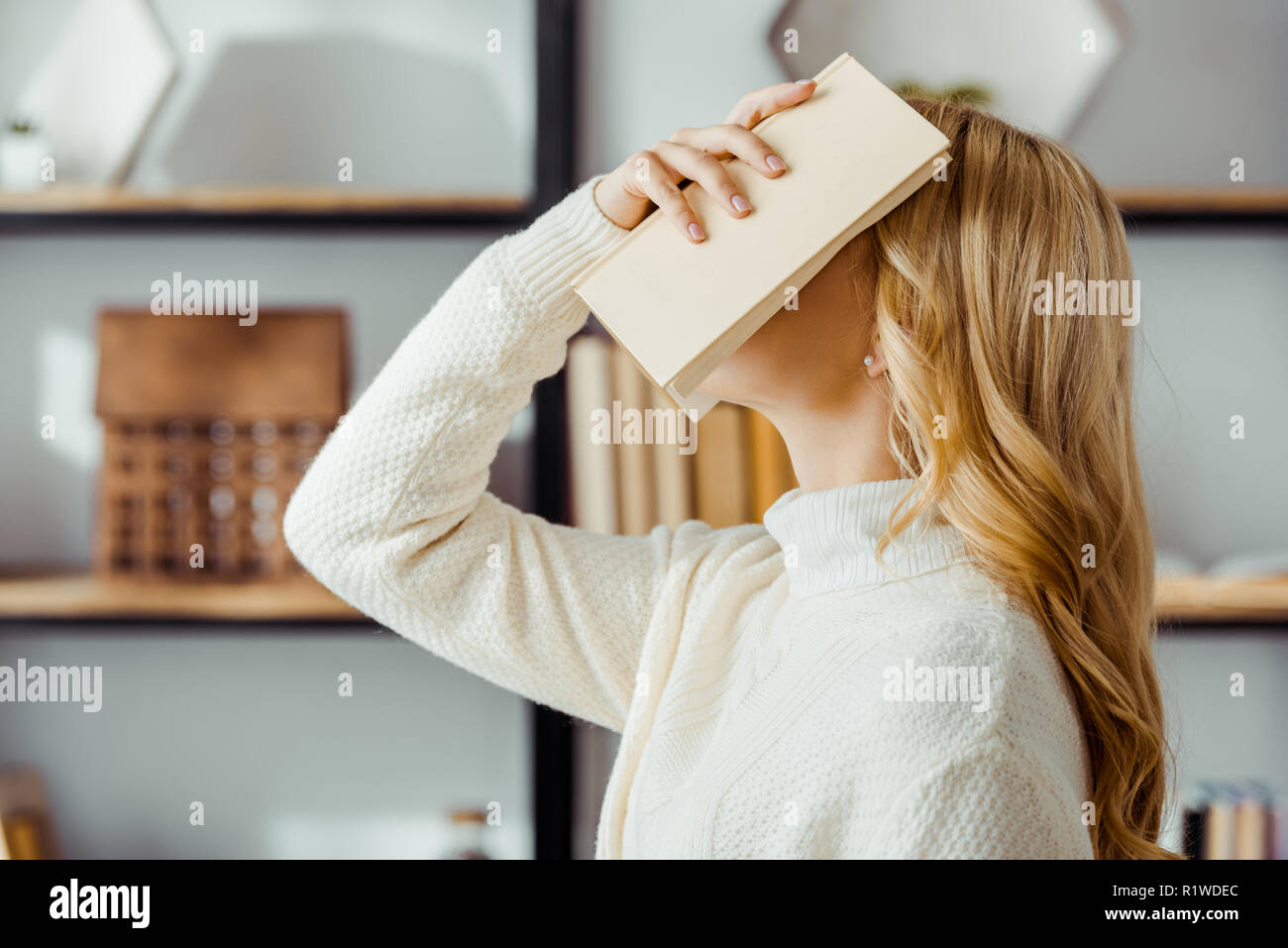 close up of blonde woman putting book on face - Stock Image
