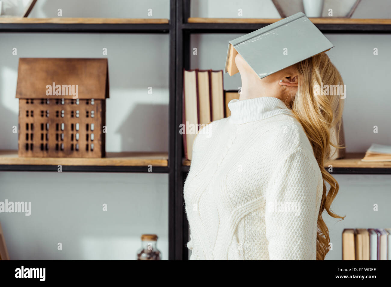 blonde woman putting book on face near rack - Stock Image