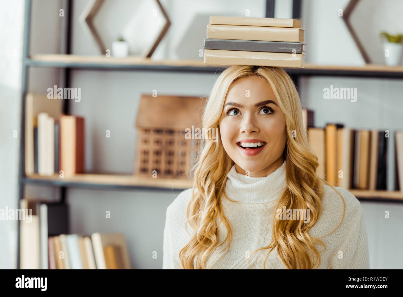 close up of funny smiling woman with books on head - Stock Image