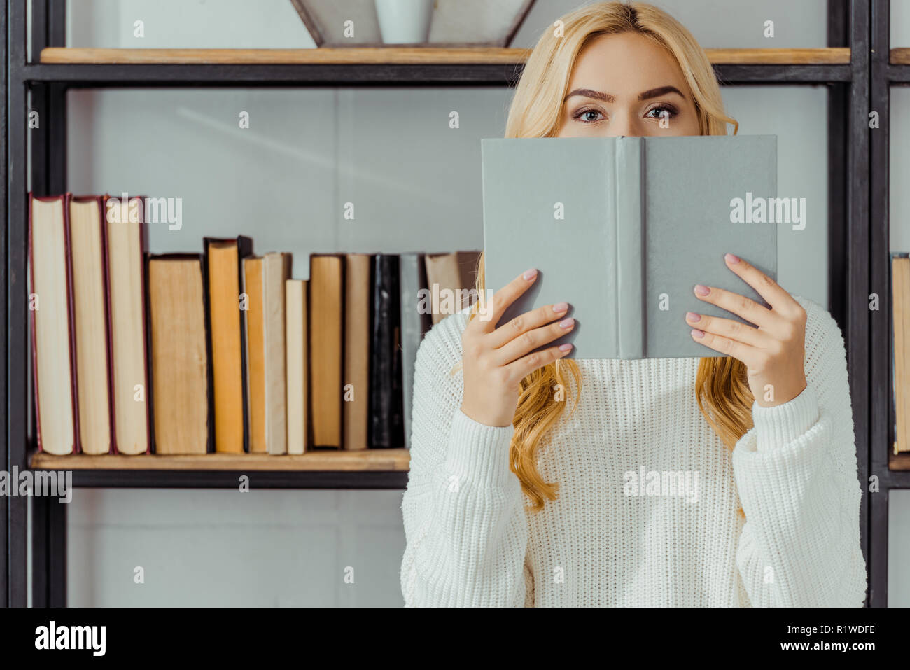 close up of blonde woman hiding face behind book - Stock Image