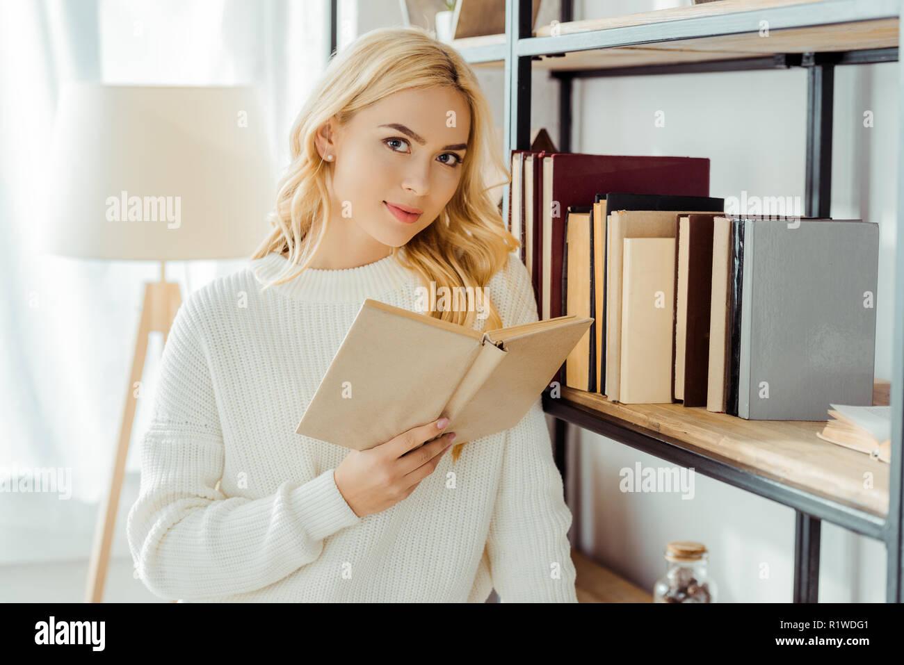close up of beautiful woman reading book near rack - Stock Image