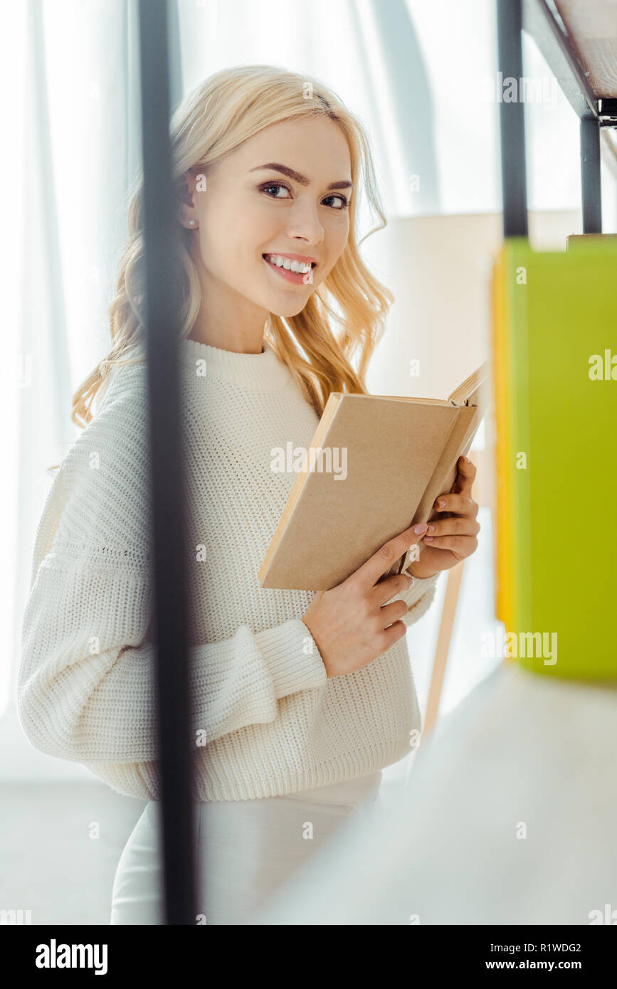 close up of beautiful smiling woman reading book in living room - Stock Image