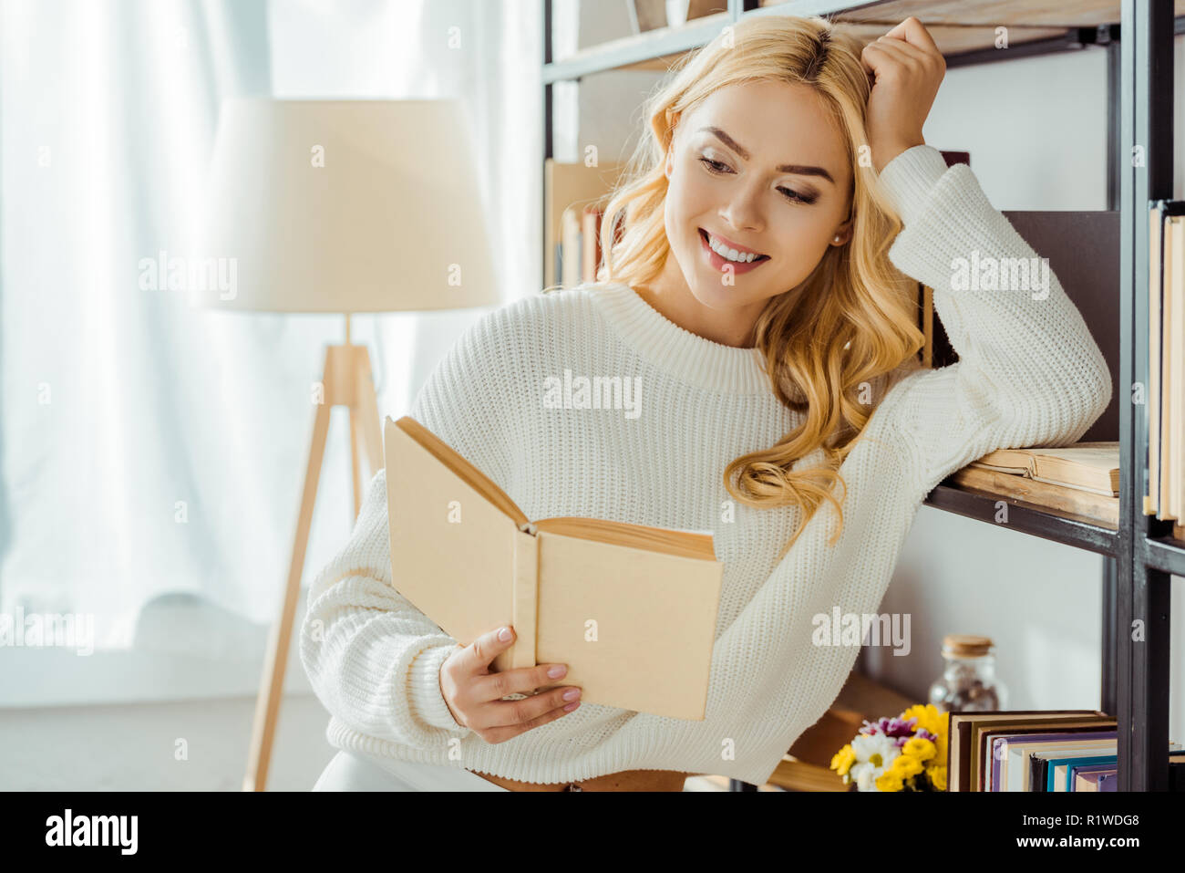 close up of beautiful smiling woman reading book near rack - Stock Image