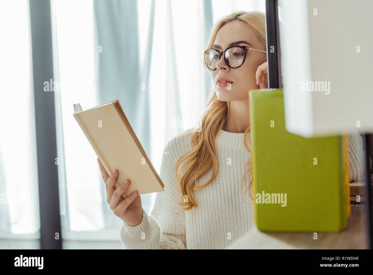 close up of beautiful adult woman in glasses reading book - Stock Image