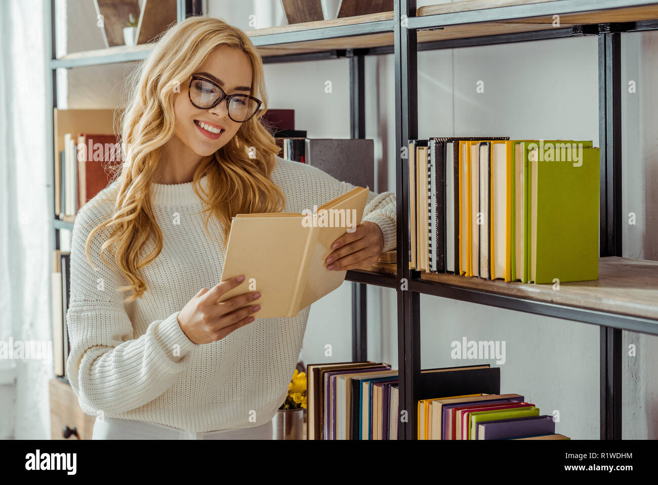 close up of smiling adult woman in glasses reading book - Stock Image