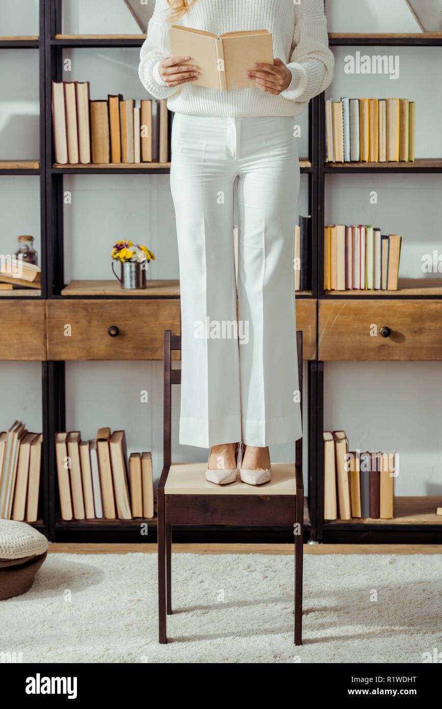 close up of adult woman standing on chair in living room and reading book - Stock Image