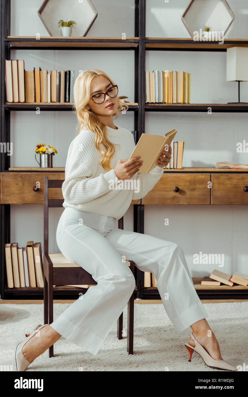 beautiful woman in glasses sitting in library and reading book - Stock Image