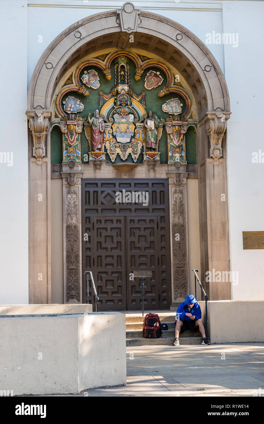 A single homeless man sits on the steps of the city library with his backpack and wearing a poncho and shorts. - Stock Image