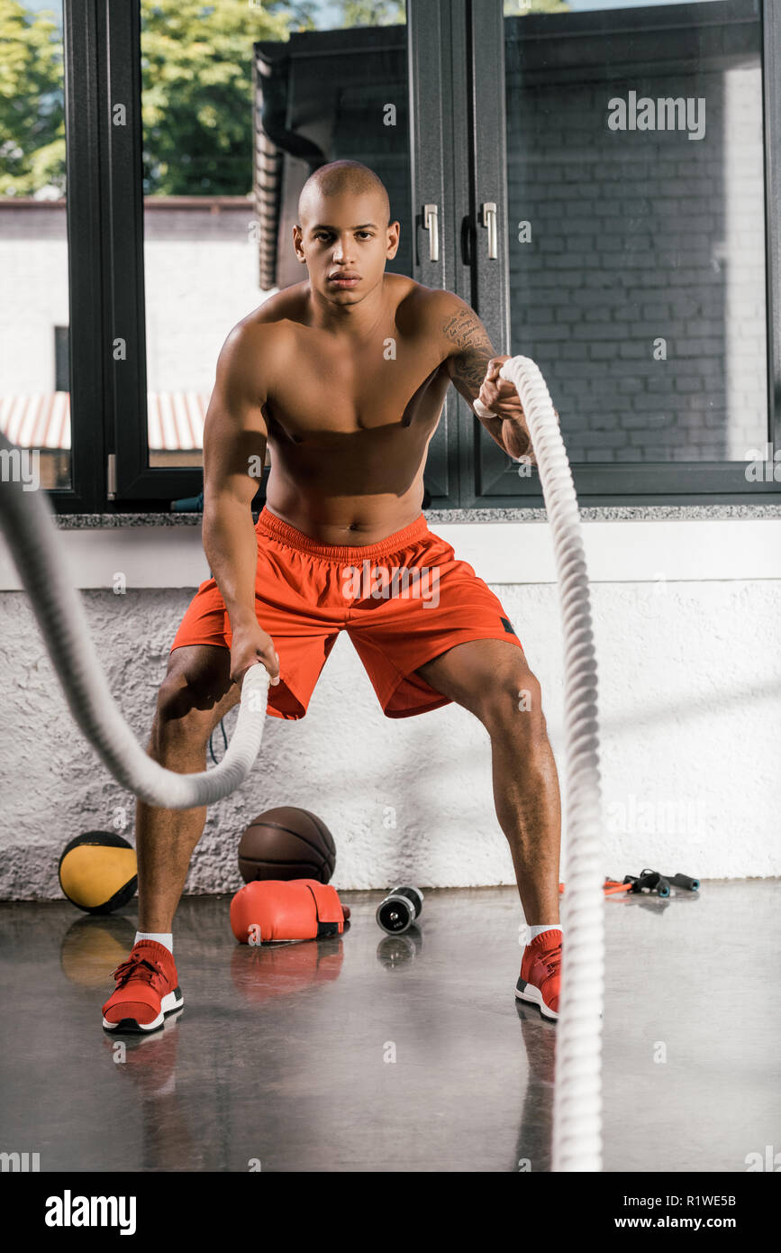 muscular shirtless african american athlete working out with battle ropes at gym - Stock Image