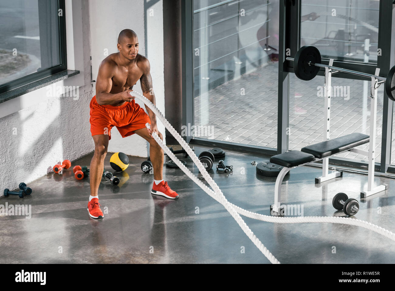 high angle view of african american athlete working out with battle ropes at gym - Stock Image