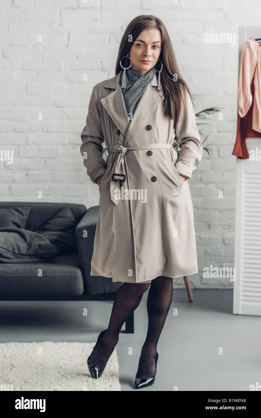 young transgender man in trench coat looking at camera at home