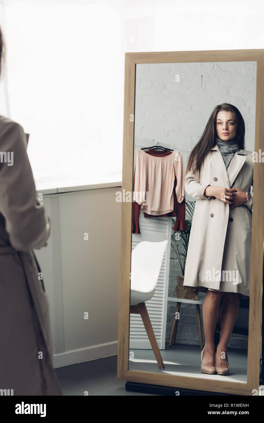 young transgender man in trench coat looking at mirror at home - Stock Image
