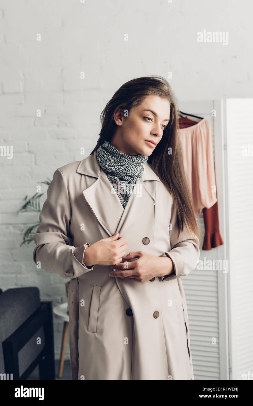 stylish young transgender man in trench coat at home - Stock Image