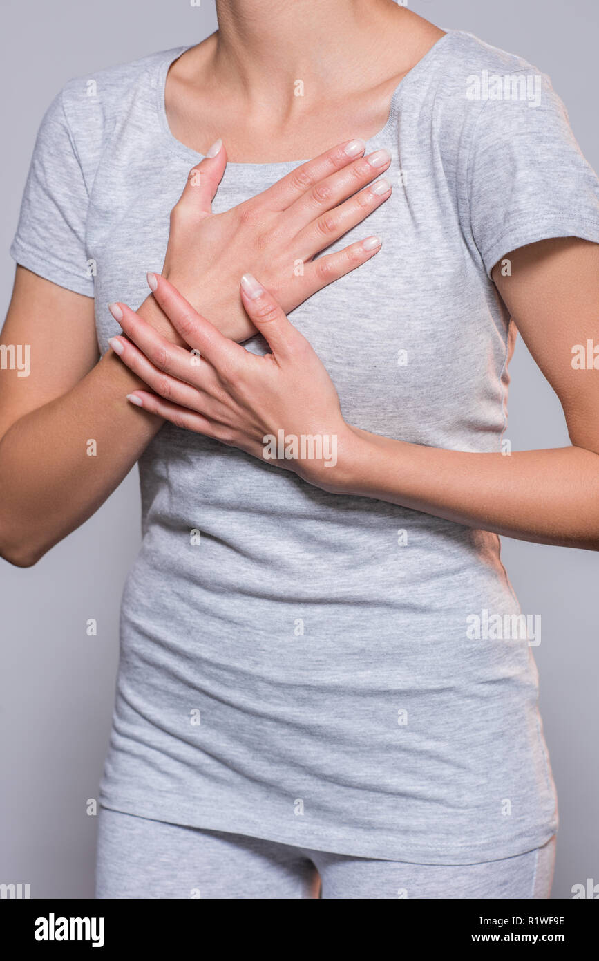 partial view of woman having heartache on grey background - Stock Image