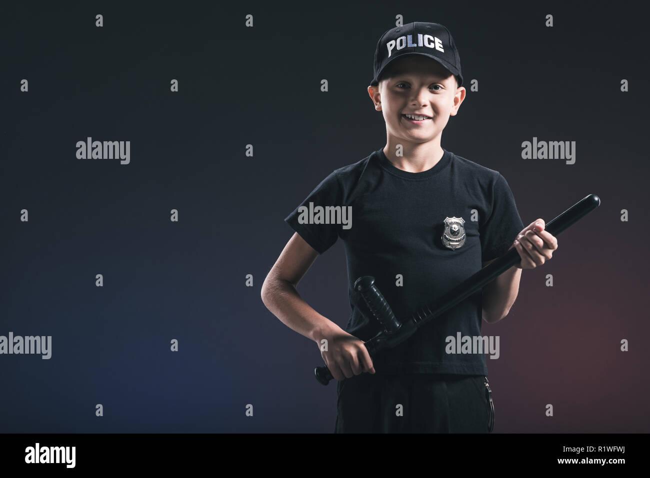 smiling preteen boy in policeman uniform with truncheon on dark backdrop - Stock Image