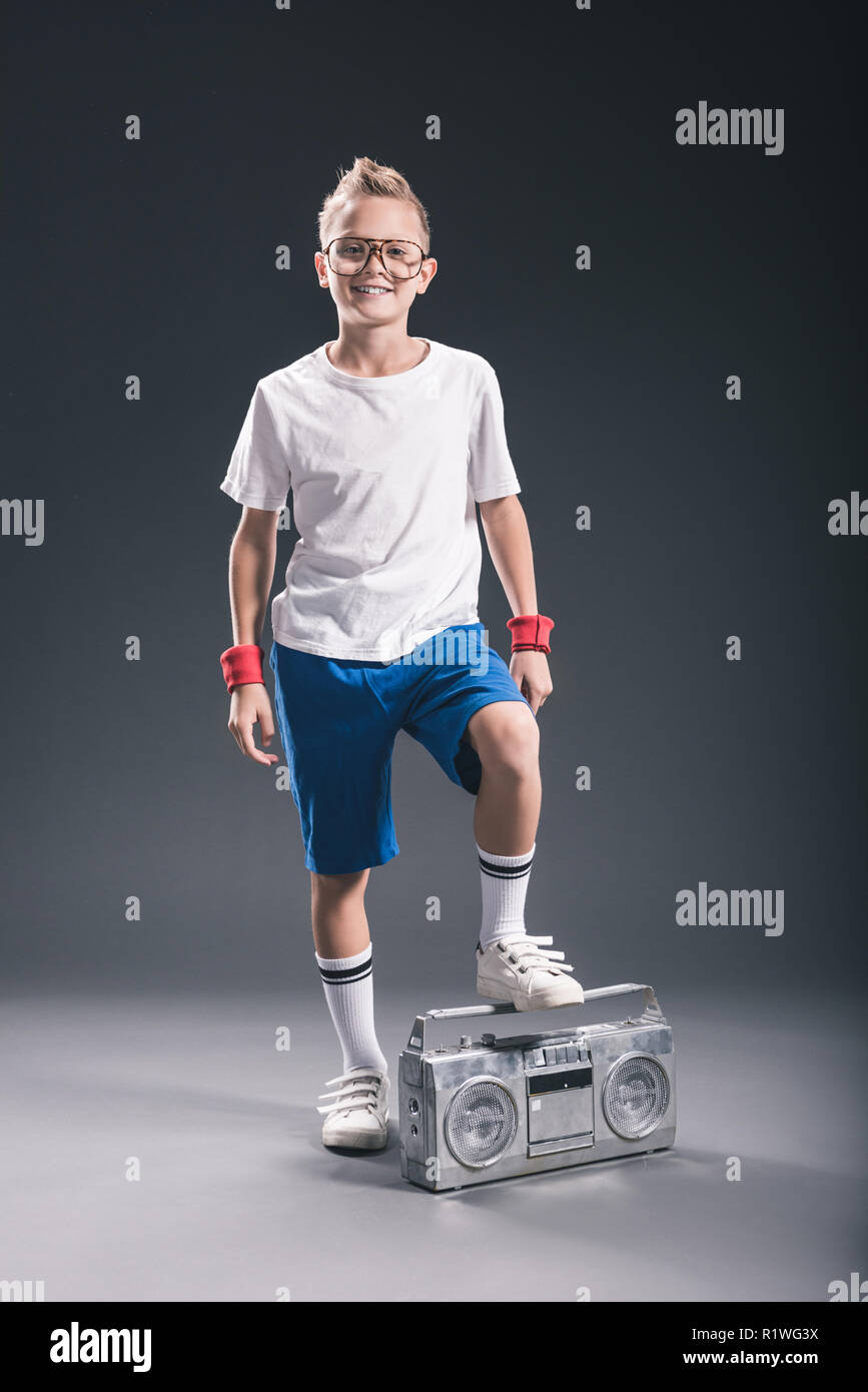 smiling preteen boy in eyeglasses with boombox posing on grey backdrop - Stock Image