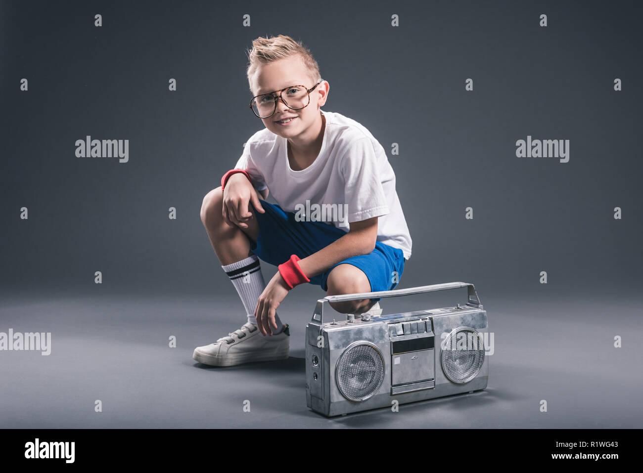 stylish preteen boy in eyeglasses with boombox posing on grey backdrop - Stock Image