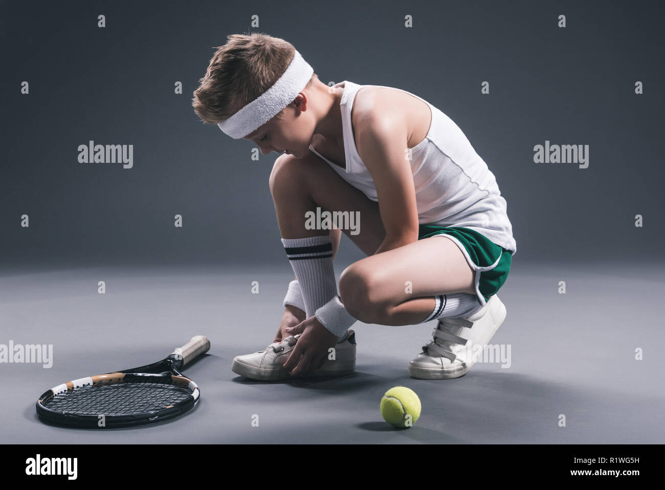 preteen boy in sportswear with tennis racket and ball on dark background - Stock Image