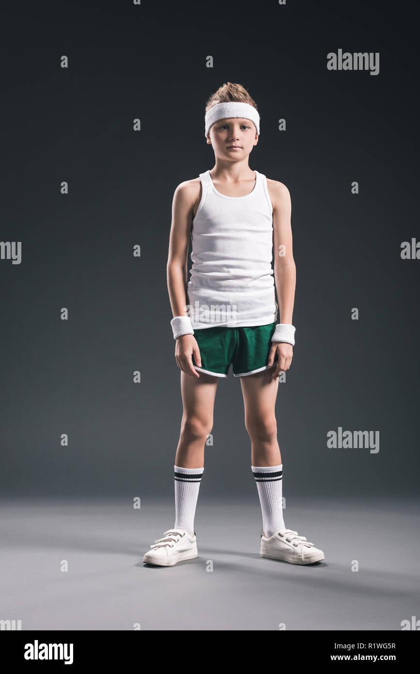 preteen boy in tennis sportswear looking at camera on grey backdrop - Stock Image