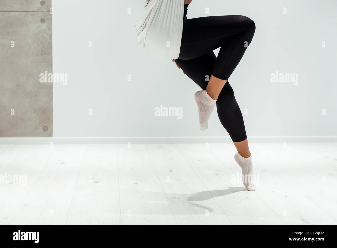 Partial view of female doing antigravity yoga in studio Stock Photo