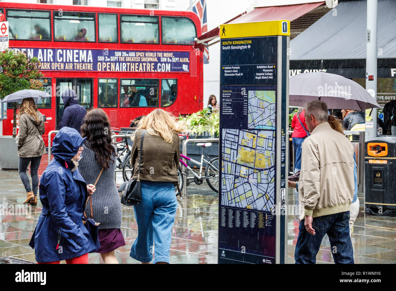 London England United Kingdom Great Britain South Kensington weather rain raining wet pavement umbrellas man woman pedestrian Legible London Wayfaring - Stock Image