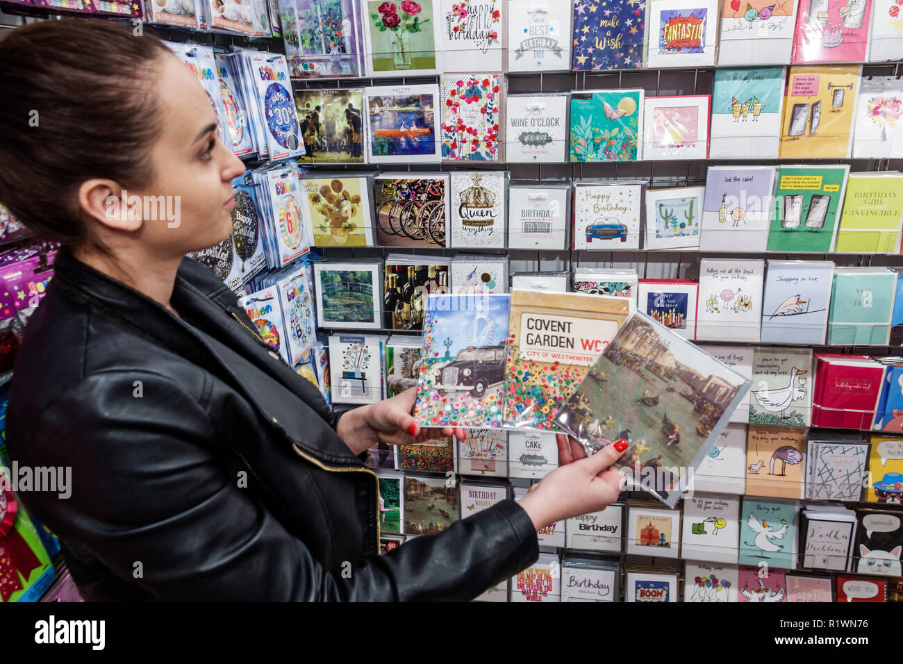 London England United Kingdom Great Britain Kensington gift shop stationery store shopping greeting cards woman choosing selecting display sale - Stock Image