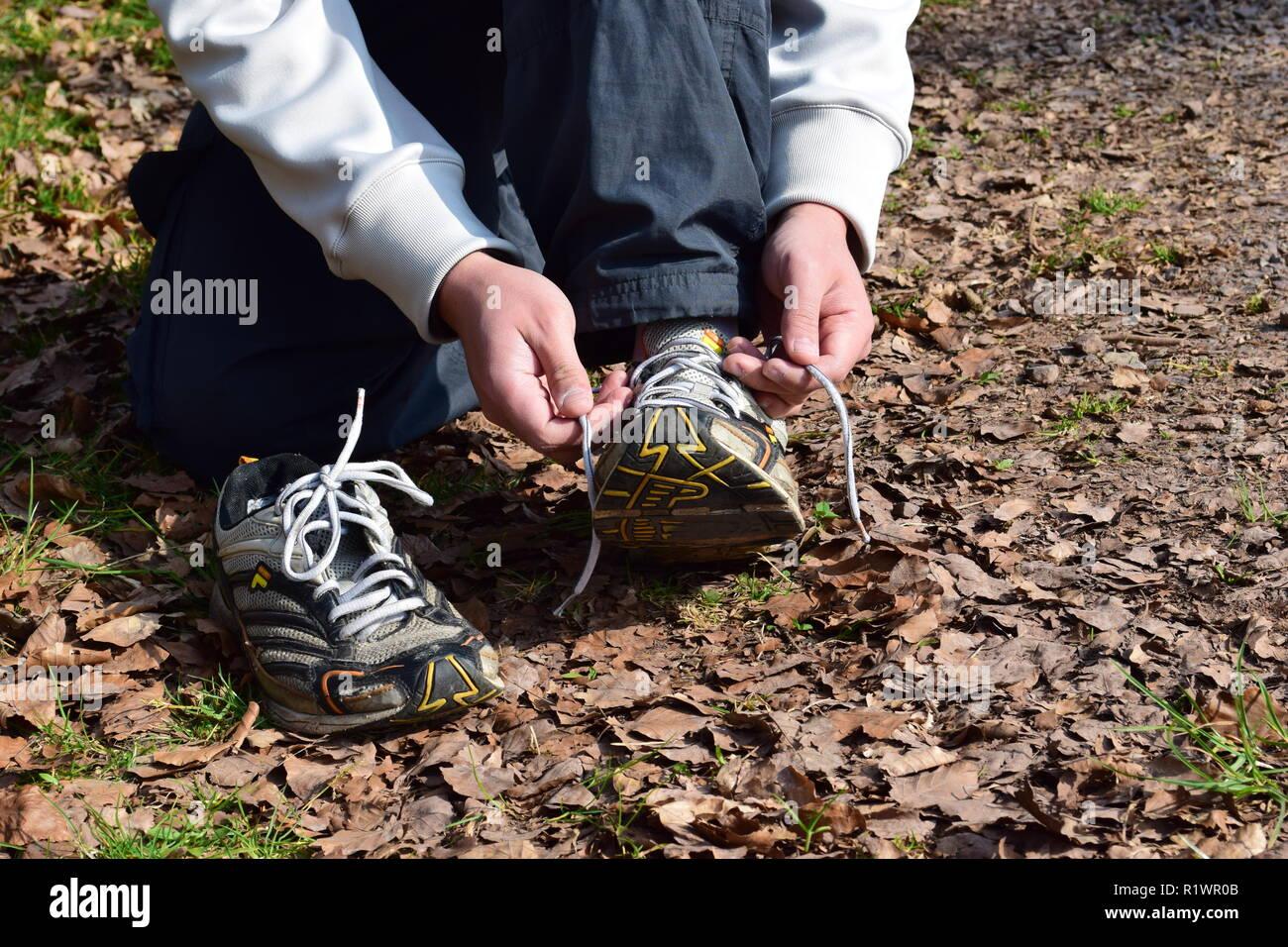 A Man is  trail running in worn out shoes with holes under the sole in the autumn forest. Ein Mann läuft im Herbstwald mit alten abgenutzten Schuhen - Stock Image