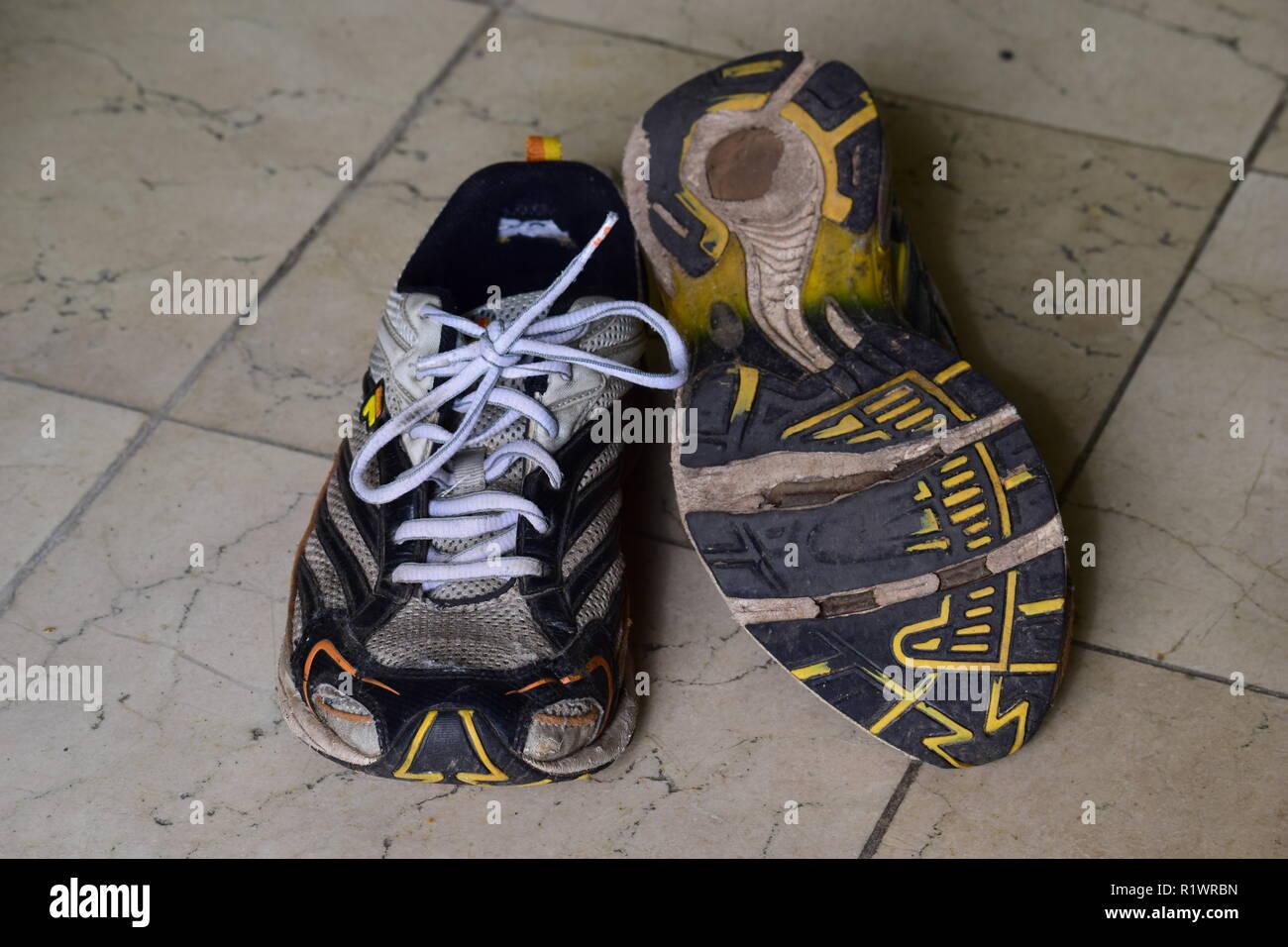 Pair of old Run and walking shoes worn out and with holes under the sole. Paar alte Lauf- und Wanderschuhe abgenutzt und mit Löchern unter der Sohle - Stock Image