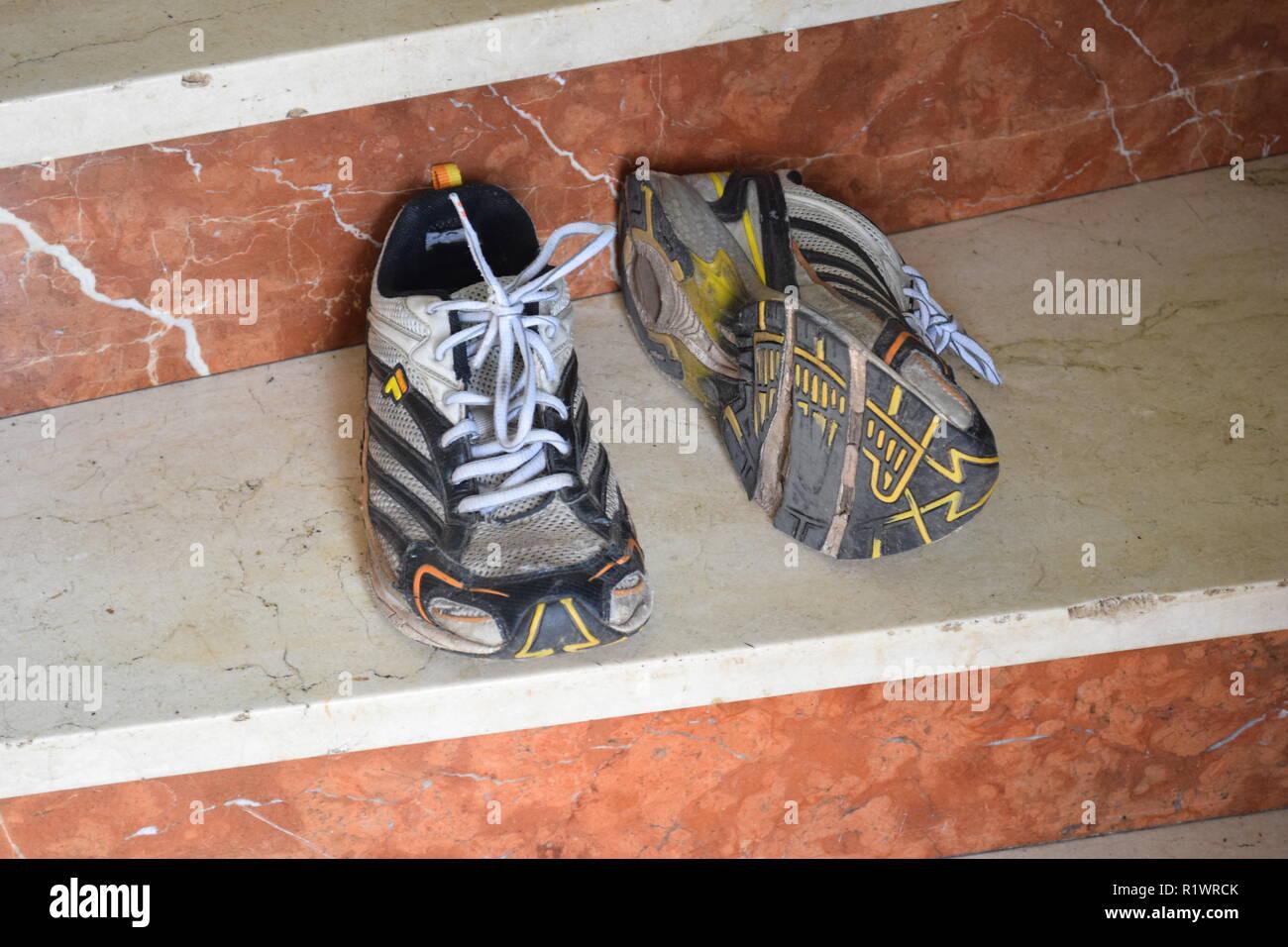 Pair of old Run and walking shoes worn out and with holes under the sole. Paar alte Lauf- und Wanderschuhe abgenutzt und mit Löchern unter der Sohle Stock Photo